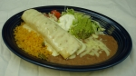 Chimichanga - Stuffed flour tortilla with your choice of beef or chicken. Deep-fried to a golden brown and topped with cheese dip, lettuce, guacamole, and pico de gallo. Served with rice and beans. <br />