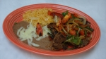 Steak Mexicano - Grilled 10 oz. T-bone steak topped with grilled onions, peppers and tomatoes. Served with rice, beans, and tortillas.